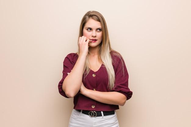 爪をかむ若いロシア人女性、神経質で非常に心配