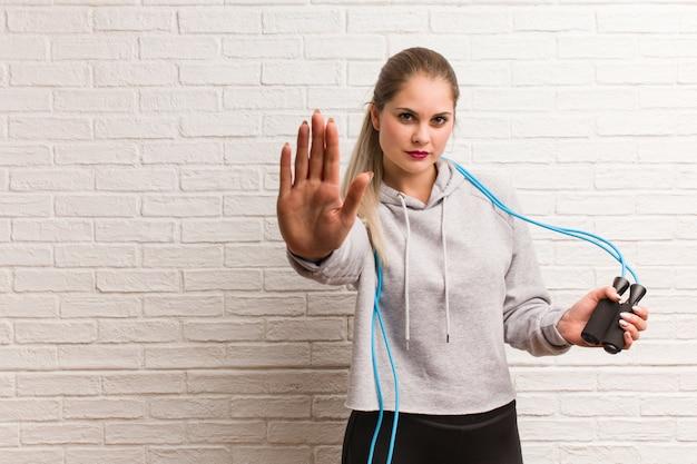 Молодая женщина фитнеса русская держа скакалку против стены кирпичей