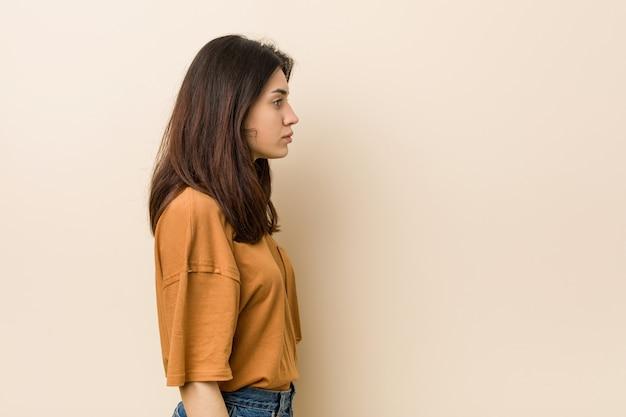 左を見つめるベージュの壁に若いブルネットの女性、横向きのポーズ。