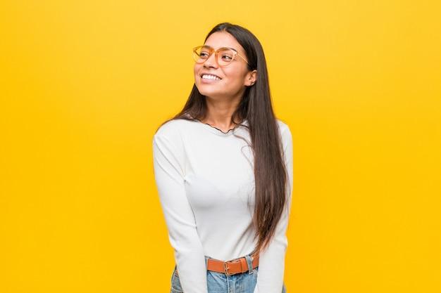 目標と目的を達成することを夢見て黄色の壁に対して若いかなりアラブの女性
