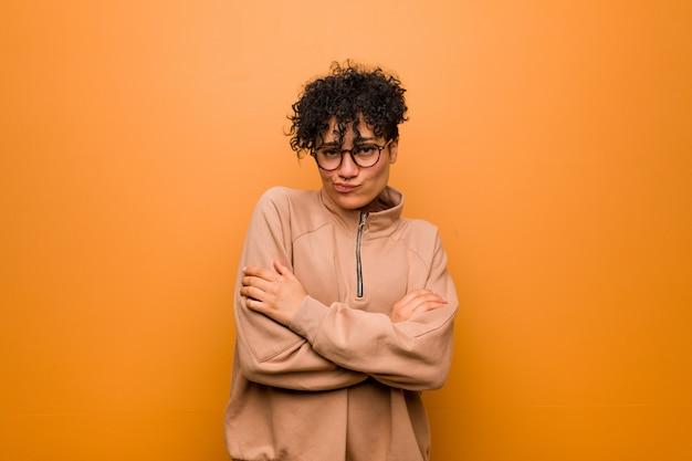 皮肉な表情でカメラで見て不幸な茶色の壁に対して若い混合アフリカ系アメリカ人女性。