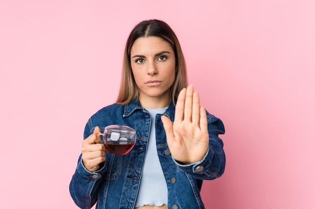 Молодая кавказская женщина держа чашку чая стоя при протягиванный знак стопа показа руки, предотвращая вас.