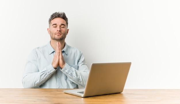 口の近くで祈って手を繋いでいる彼のラップトップで働く若いハンサムな男は自信を持って感じています。