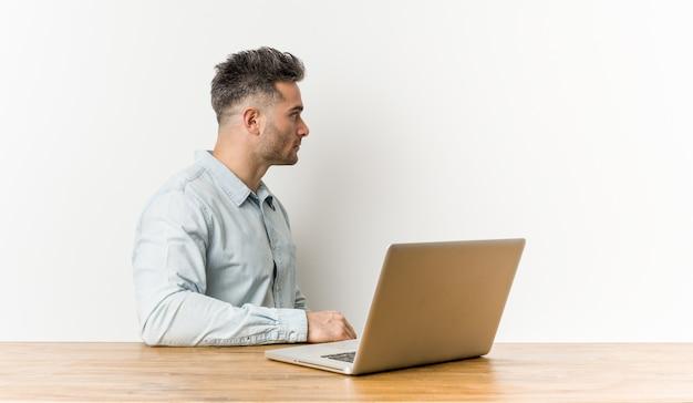 若いハンサムな男が彼のラップトップを左に見つめて作業、横向きのポーズ。