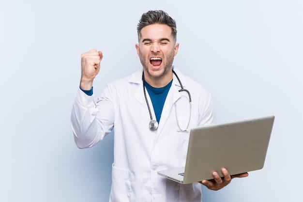 Кавказский врач мужчина держит ноутбук аплодисменты беззаботной и взволнован. концепция победы.