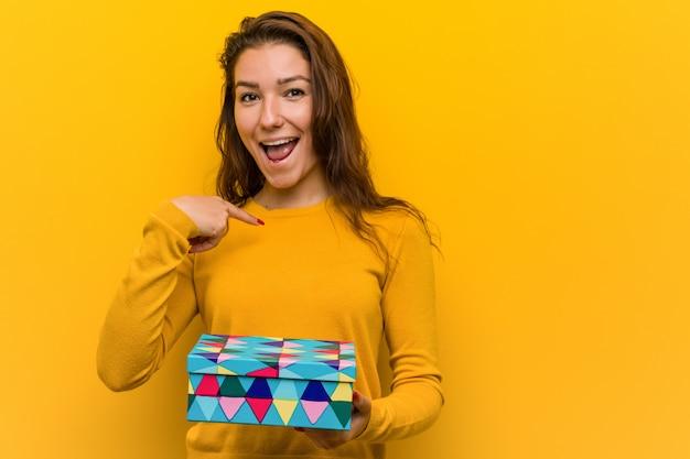贈り物を持って若いヨーロッパの女性は、自分自身を指して驚いて、広く笑っています。