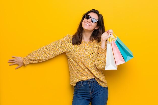 Молодая кавказская женщина идя ходить по магазинам