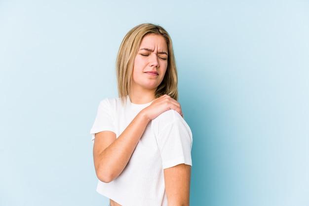 肩の痛みを持っている分離された若い金髪白人女性。