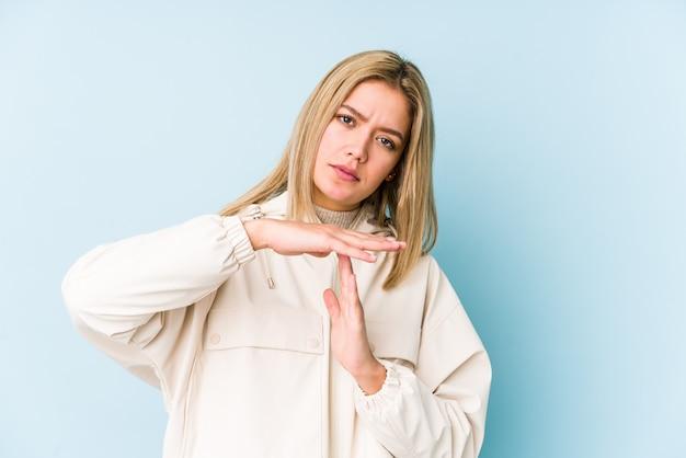 若いブロンドの白人女性は不満で顔をしかめ顔を分離し、腕を組んでいます。
