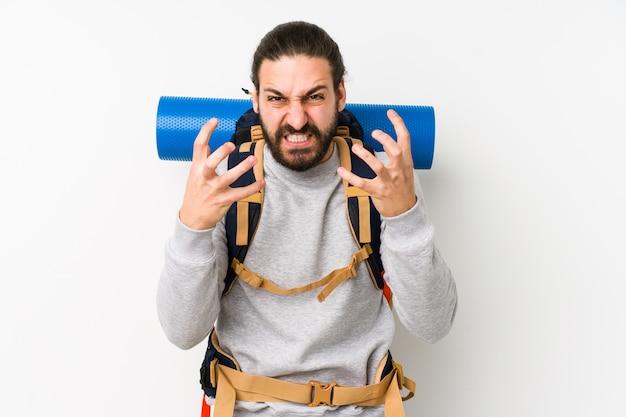 Молодой рюкзаком человек, изолированные на белой стене расстроен, кричать с напряженными руками.
