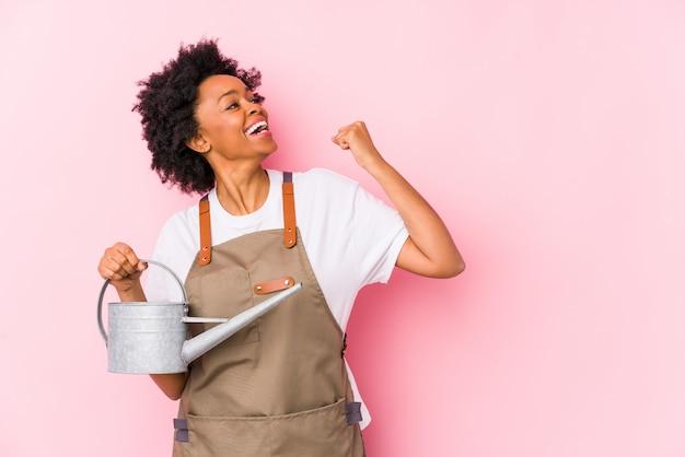Молодой афро-американский садовник поднимая кулак после победы, концепцию женщины победителя.