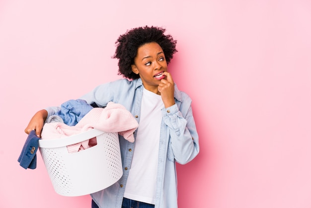 洗濯をしている中年のアフリカ系アメリカ人女性は、コピースペースを見て何かについてリラックスした思考を分離しました。