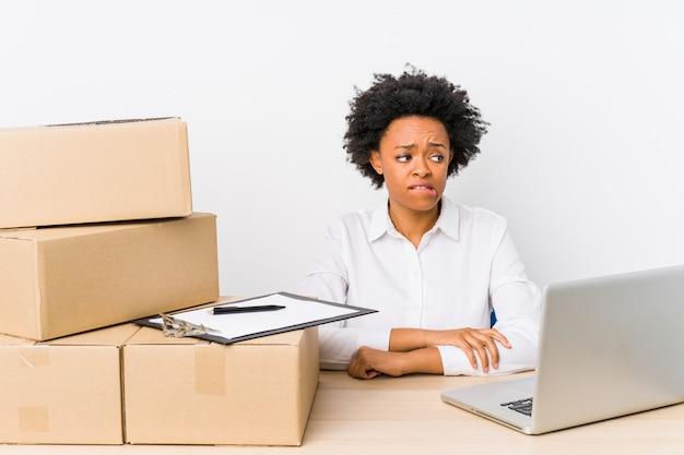 倉庫管理者は、ラップトップで配達を確認し、混乱し、疑念を抱き、不安を感じています。
