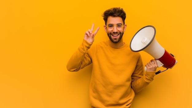 Молодой человек держит мегафон весело и счастливо делает жест победы