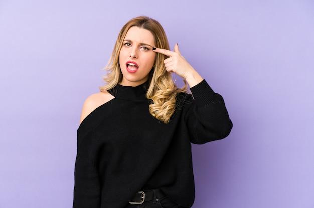 Молодая белокурая изолированная женщина показывая жест разочарования с указательным пальцем.
