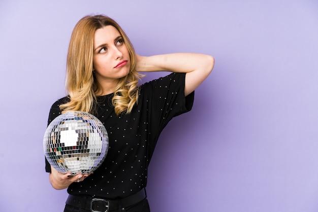 Молодая белокурая женщина держа шарик партии ночи изолировала касаться задней части головы, думая и делая выбор.