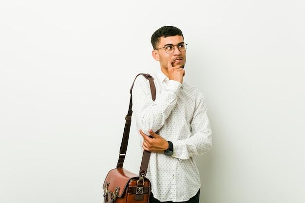 Молодой испанец случайный деловой человек спокойно думать о чем-то, глядя на копией пространства.
