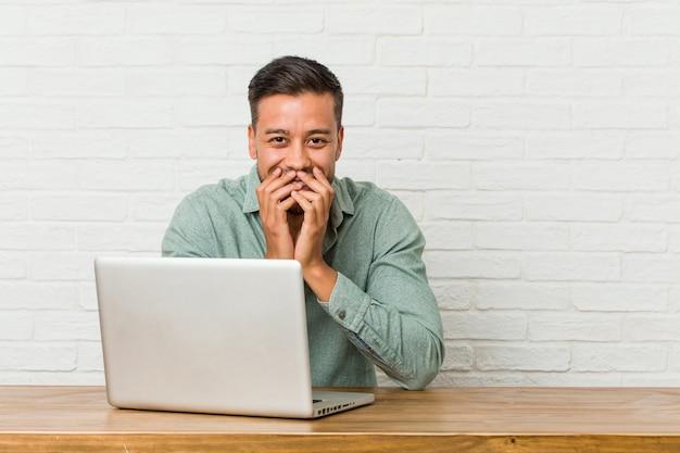 Молодой филиппинский человек, сидящий, работающий со своим ноутбуком, смеющийся о чем-то, покрывающем рот руками.