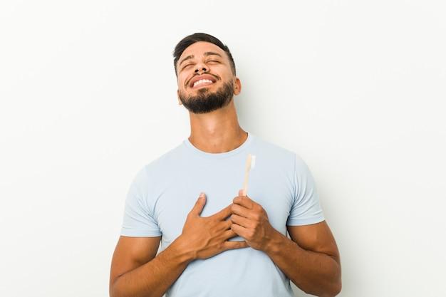 歯ブラシを持った南アジアの若い男は、胸に手をつないで大声で笑います。