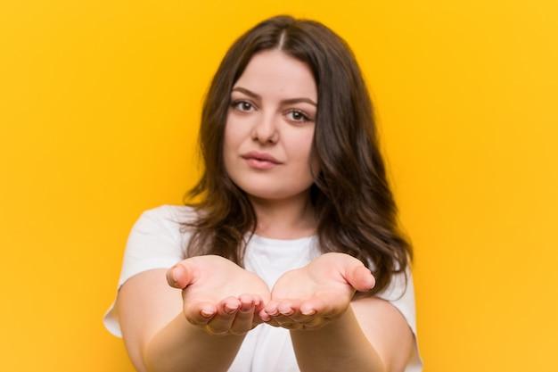 Молодая соблазнительная женщина плюс размер держит что-то с ладонями