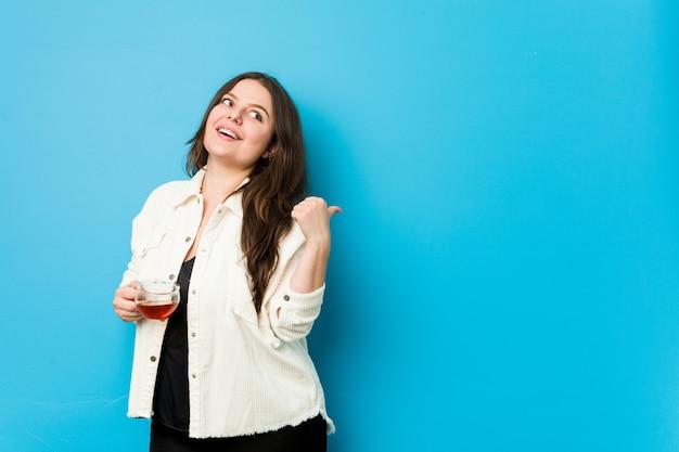ティーカップを保持している若い曲線の女性は、親指の指を離れて、笑って屈託のないです。