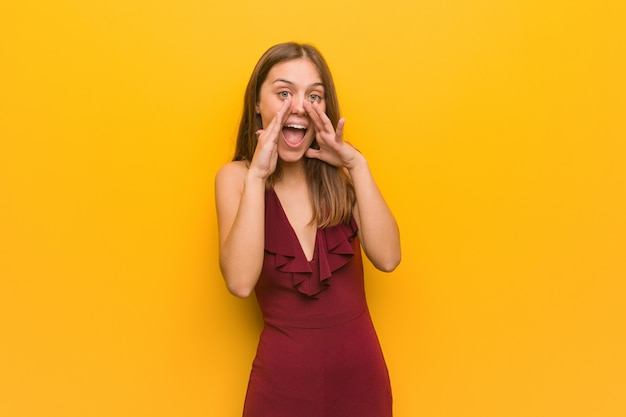 正面に幸せな何かを叫んでいるドレスを着ている若いエレガントな女性