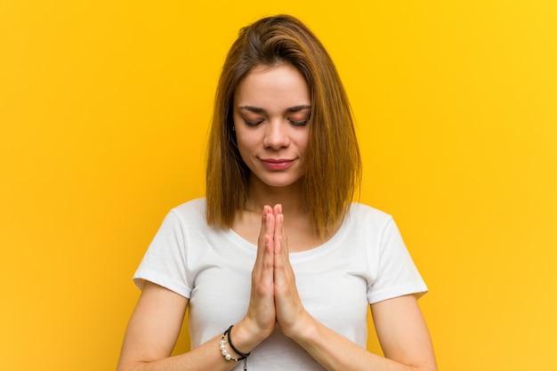 口の近くで祈って手を繋いでいる若い自然な白人女性は自信を持って感じています。