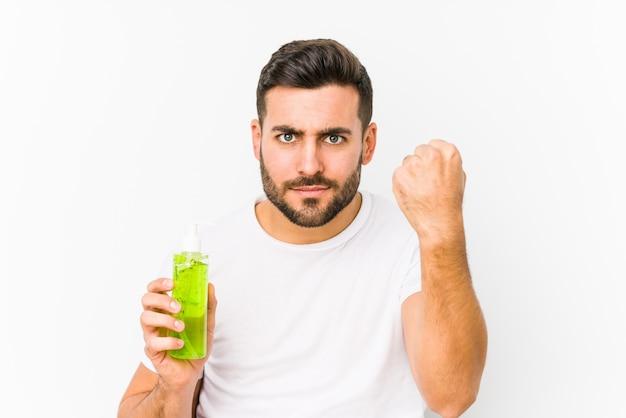 アロエベラと保湿剤を保持している若い白人男は積極的な表情で拳を見せて分離しました。