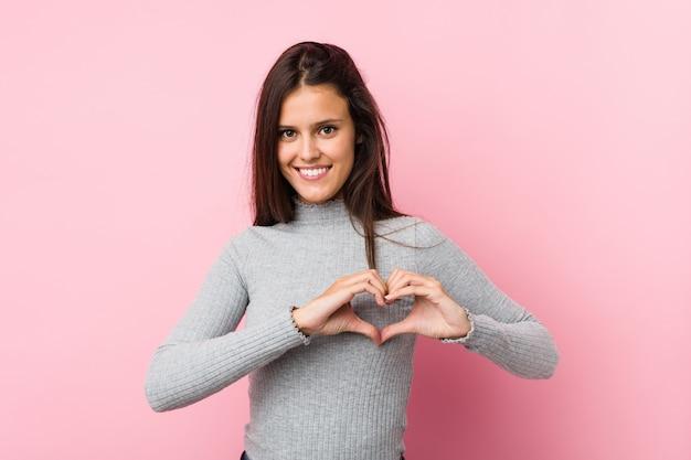 Молодая милая женщина усмехаясь и показывая форму сердца с руками.