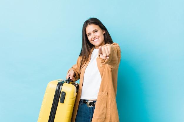 Молодая кавказская женщина держа улыбки чемодана жизнерадостные указывая к фронту.