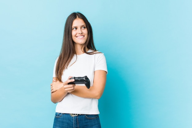 組んだ腕に自信を持って笑顔のゲームコントローラーを保持している若い白人女性。