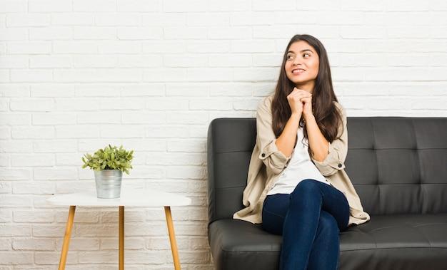 ソファに座っている若いアラブの女性は、あごの下で手をつないで、喜んで脇を見ています。