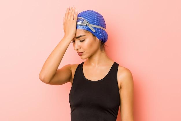 Молодая арабская женщина пловца изолировала забывать что-то, шлепая лоб ладонью и закрывая глаза.