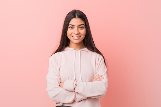 自信を持って、決意を持って腕を組んでいるカジュアルなスポーツルックを着ている若いかなりアラブの女性。