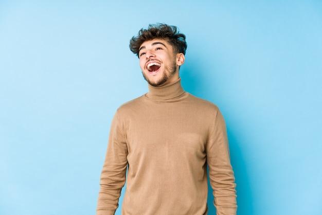 Молодой аравийский человек изолировал расслабленный и счастливый смех, шея растягивается, показывая зубы.