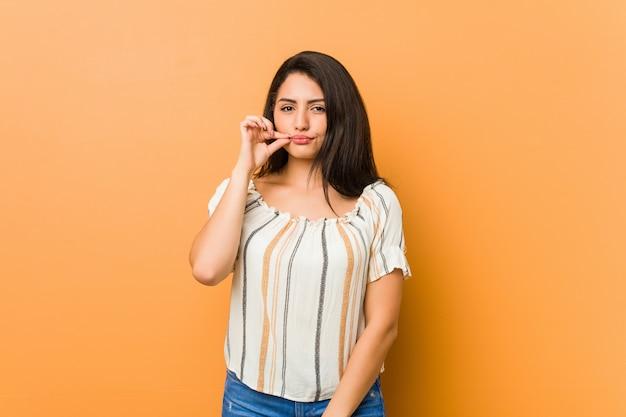 Молодая соблазнительная женщина с пальцами на губах, сохраняя в тайне.