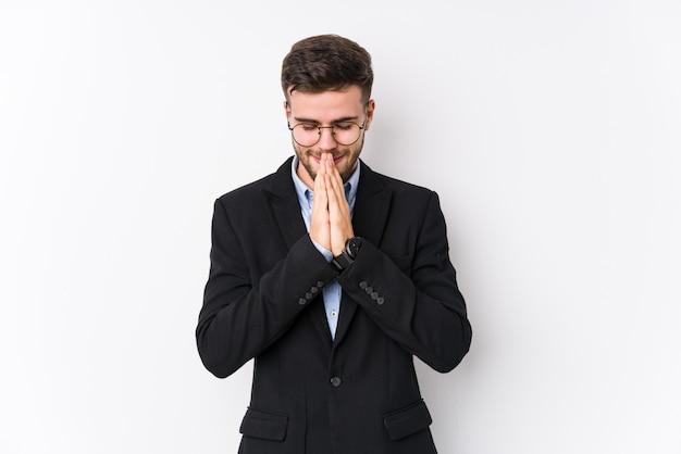 孤立した白い壁でポーズをとる若い白人ビジネスマン口の近くで祈って手を繋いでいる若い白人ビジネスマンは自信を持っています。