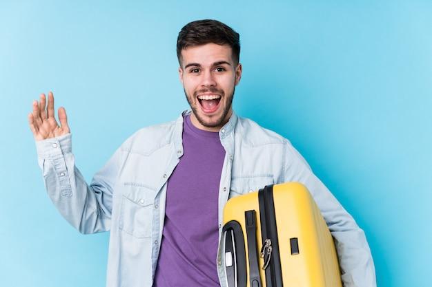 Молодой человек кавказской путешественник, держа чемодан изолированы получать приятный сюрприз, возбужденных и поднимать руки.