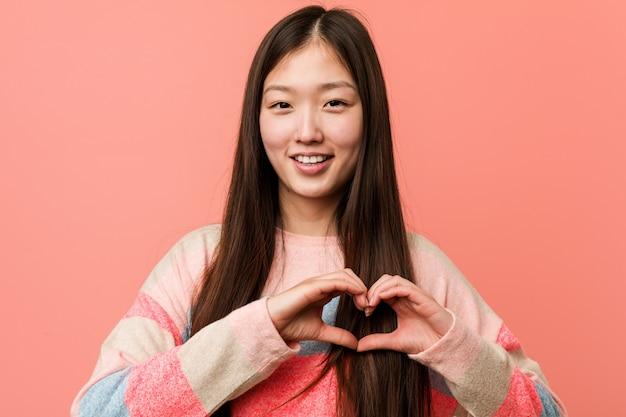 若いクールな中国の女性は笑みを浮かべて、彼の手で心臓の形を示します。