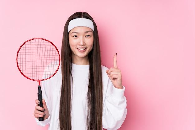 Молодая китайская женщина играя бадминтон изолировала показывать одно с пальцем.