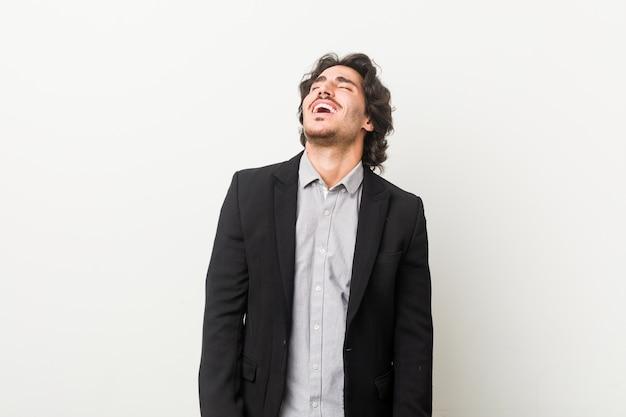 白い壁に対して若いビジネスマンリラックスして幸せな笑い、首を伸ばして歯を見せて。