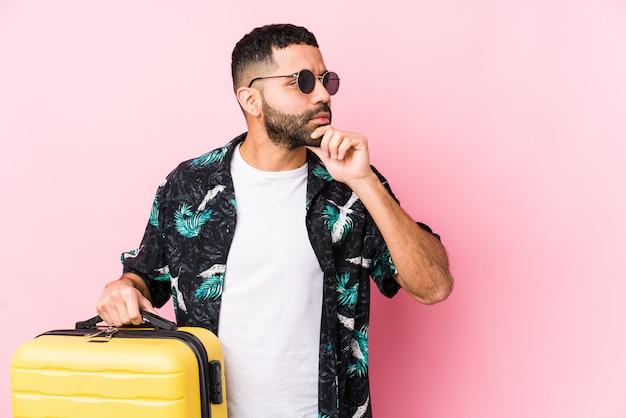 疑わしいと懐疑的な表情で横向きのスーツケースを保持している若いラテン男。