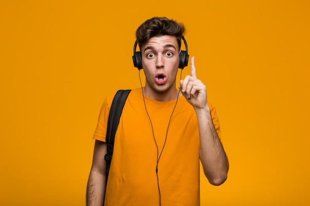 ヘッドフォンで音楽を聴く若いクールな学生男は、コピースペースを見て何かを考えてリラックスしました。