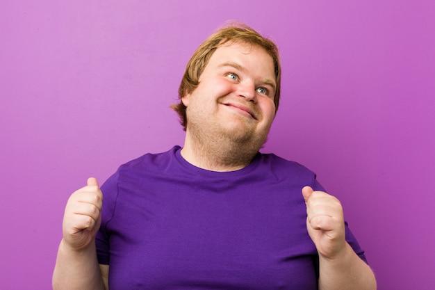 若い本物の赤毛のデブ男が拳を上げ、幸せと成功を感じています。勝利のコンセプト。