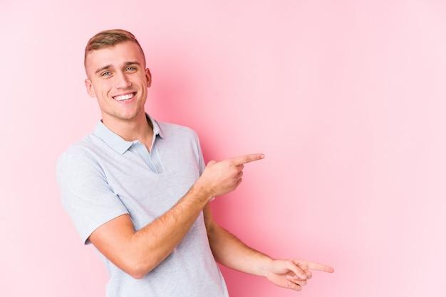 Молодой кавказский человек изолировал возбужденный указывать с указательными пальцами прочь.