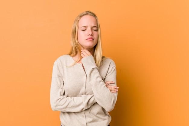 キュートで自然なティーンエイジャーの女性は、ウイルスや感染症により喉の痛みに苦しんでいます。