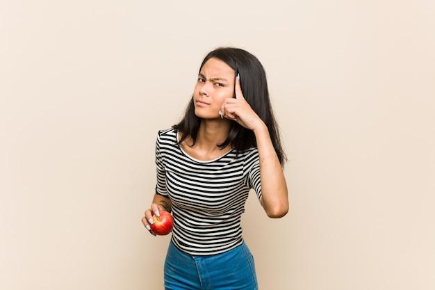 人差し指で失望のジェスチャーを示すリンゴを保持している若いアジア女性。