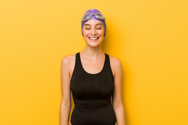 Молодой пловец кавказской женщины смеется и закрывает глаза, чувствует себя расслабленным и счастливым.