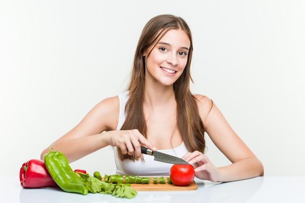 Молодая кавказская женщина держа нож и режа овощи