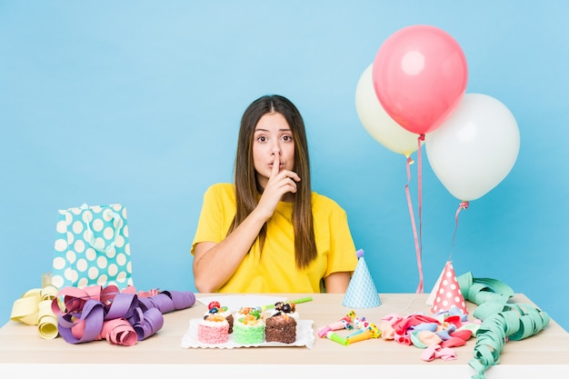 Молодая кавказская женщина организуя день рождения держа в секрете или прося безмолвие.